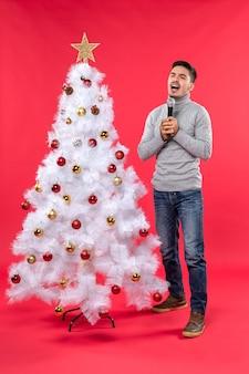 Kerstsfeer met positieve man gekleed in spijkerbroek staan in de buurt van versierde kerstboom en zingt enthousiast zijn favoriete liedje