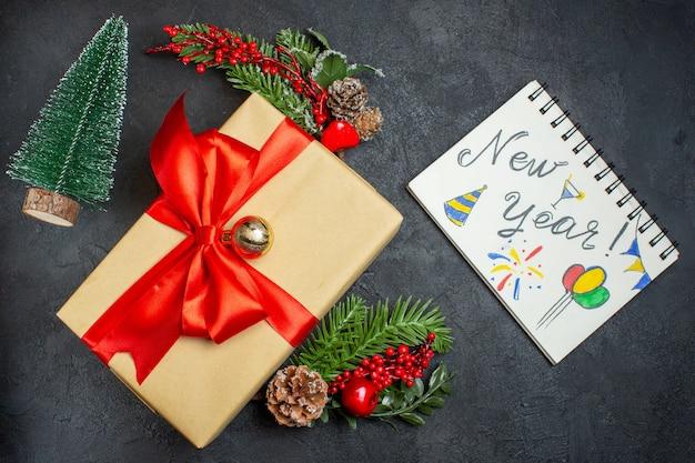 Kerstsfeer met prachtige cadeaus met boogvormig lint en dennentakken decoratie accessoires xsmas sok notitieboekje met nieuwjaarstekeningen op een donkere achtergrond