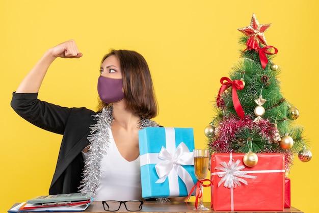 Kerstsfeer met trotse mooie dame in pak met medisch masker en geschenk in het kantoor op geel te houden