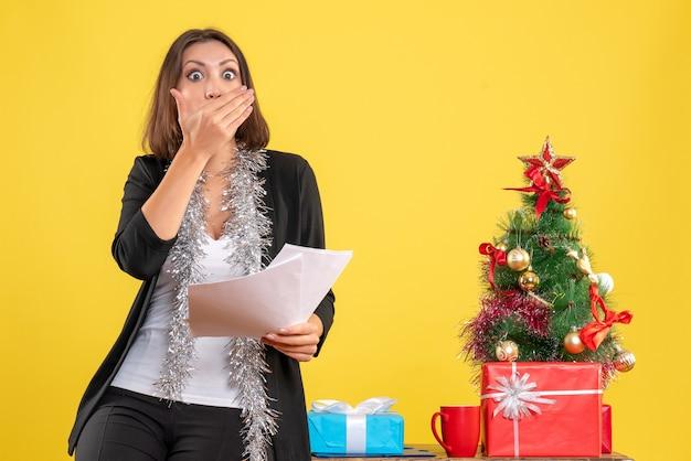 Kerstsfeer met verbaasde mooie dame die in het kantoor staat en documenten in het kantoor op geel houdt