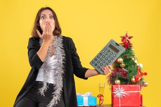 Kerstsfeer met verrast nerveuze mooie dame permanent in het kantoor en rekenmachine in het kantoor op geel te houden
