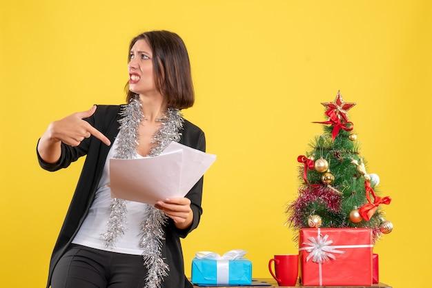 Kerstsfeer met verwarde mooie dame die in het kantoor staat en documenten in het kantoor op geel wijst