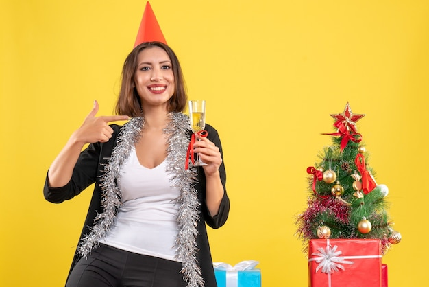 Kerstsfeer met verwarde mooie dame die wijn in het kantoor op geel houdt