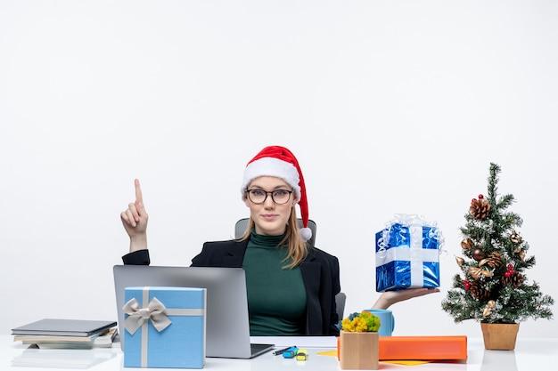 Kerstsfeer met zelfverzekerde en serieuze jonge vrouw met kerstman hoed en het dragen van een bril zittend aan een tafel met cadeau wijst naar boven op witte achtergrond