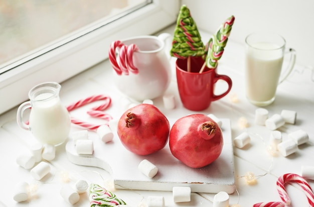 Kerstsnoepjes granaatappel, melk, marshmallows, snoepjes bij het raam