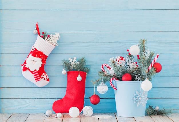 Kerstsok en dennentakken in blauwe buchet op blauwe woode