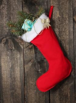 Kerstsok met geschenken op houten achtergrond