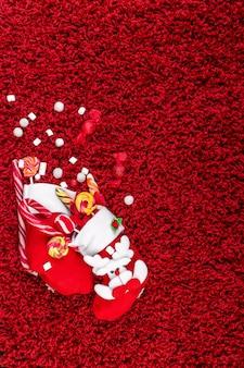 Kerstsokken vol snoep en snoep op rode wollige ondergrond plat leggen