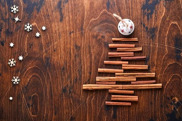 Kerstspar gemaakt van gevormde kaneel en anijskruiden met rode en groene kerstballen op houtachtergrond voor uw kerstgroeten. bovenaanzicht met kopie ruimte.