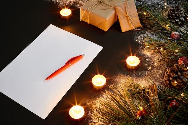 Kerstspeelgoed, brandende kaarsen en notitieboekje liggend in de buurt van groene sparren tak op zwarte achtergrond bovenaanzicht. ruimte kopiëren. stilleven. plat leggen. nieuwjaar