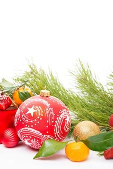 Kerstspeelgoed, een dennentak en kerstversieringen op een witte achtergrond, close-up, kopieerruimte