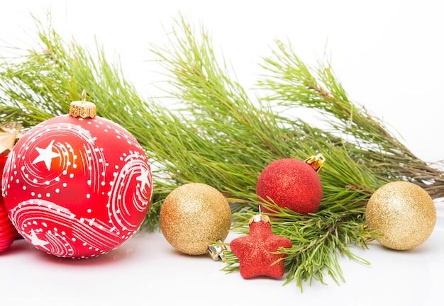 Kerstspeelgoed, een dennentak en kerstversieringen op een witte achtergrond, close-up