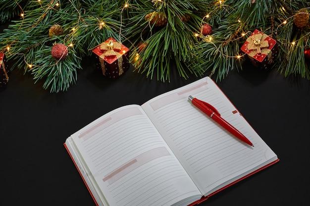 Kerstspeelgoed en notebook liggen in de buurt van groene sparren tak op zwarte achtergrond bovenaanzicht. ruimte kopiëren. stilleven. plat leggen. nieuwjaar