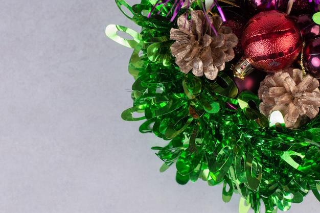Kerstspeelgoed met dennenappels op witte tafel.