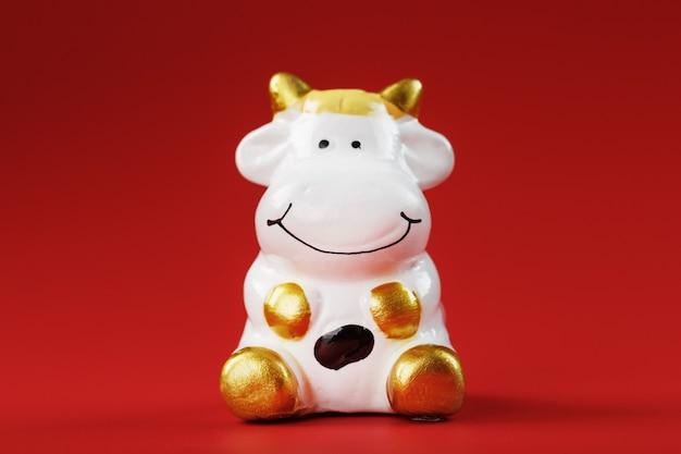 Kerstspeelgoed van een koe gemaakt van keramiek op een rode achtergrond