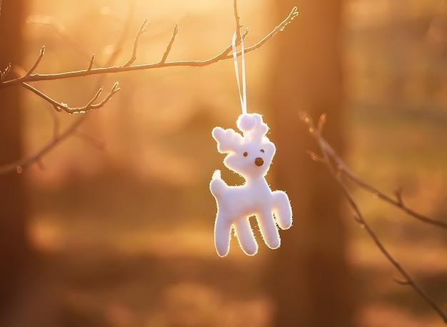 Kerstspeelgoed wit grappig pluizig hert dat buiten aan een boomtak hangt in het zonsonderganglicht