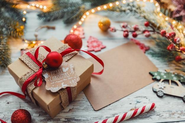 Kerstspeelgoedgeschenken met een ambachtelijke kaart voor het invoegen van tekst op een houten achtergrond met sneeuwvlokken