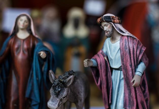 Kerststal met jozef-figuur naast ezel en moeder maria kerstseizoenconcept