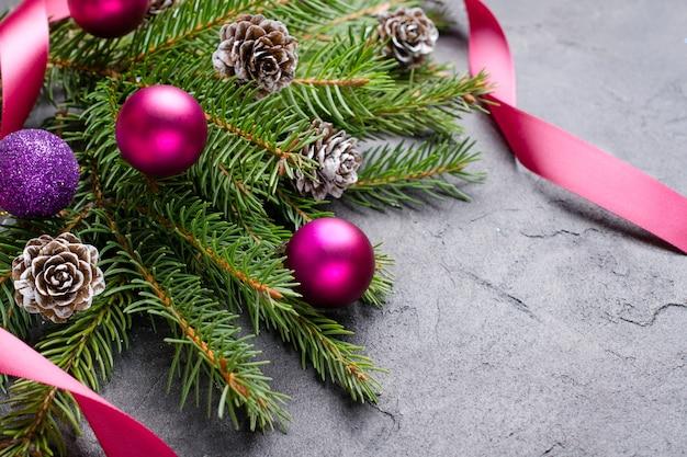 Kerststeen met tak van een dennenboom, dennenappels en decoraties