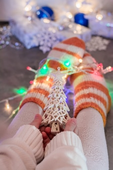 Kerststemming. een warm gekleed kind houdt een dennenornament in zijn handen