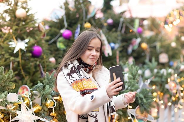 Kerststemming jonge meisjes maken een selfie op een smartphone tegen de achtergrond van licht