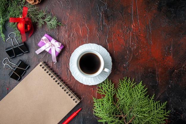 Kerststemming met decoratieaccessoires van dennentakken en cadeau naast notitieboekje met pen op donkere achtergrond
