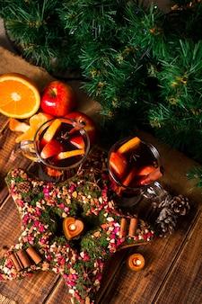 Kerstster in de buurt van glühwein met fruit en kruiden op houten tafel