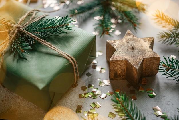 Kerststerkaars met kerstboomtakken en geschenkdoos verpakt in kraftpapier