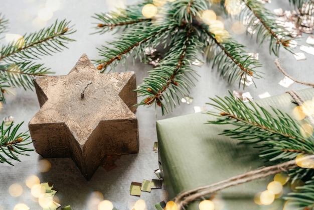 Kerststervormige kaars met kerstdennentakken en geschenkdoos verpakt in kraftpapier