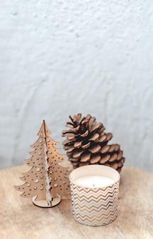 Kerststilleven met een houten kerstboom, een grote dennenappel en een kaars