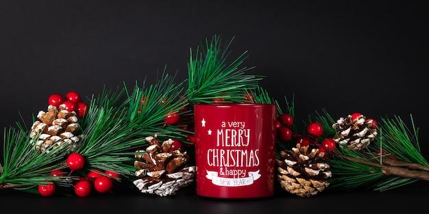 Kerststilleven met rode kaars en dennentakken met denneappels en hulstbessen op donker