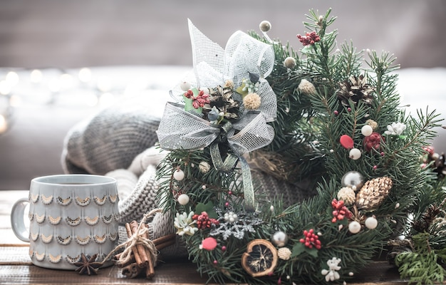 Kerststilleven van kerstbomen en decoraties, feestelijke krans op een achtergrond van gebreide kleding en mooie bekers, kerstkruiden