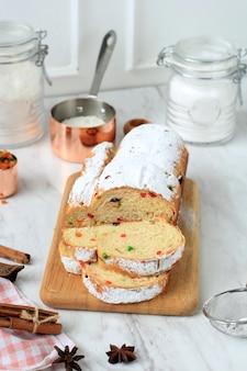 Kerststol. traditioneel zoet fruitbrood duits met poedersuiker. kerstvakantie tafel setting, versierd met mini boom kerstboom en decoratie.