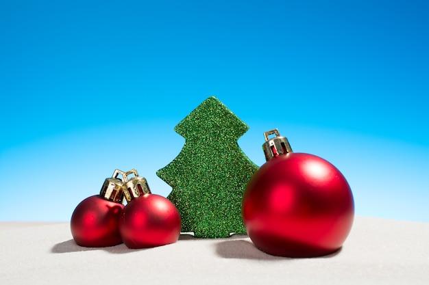 Kerststuk speelgoed glazen ballen en fir tree op een strand
