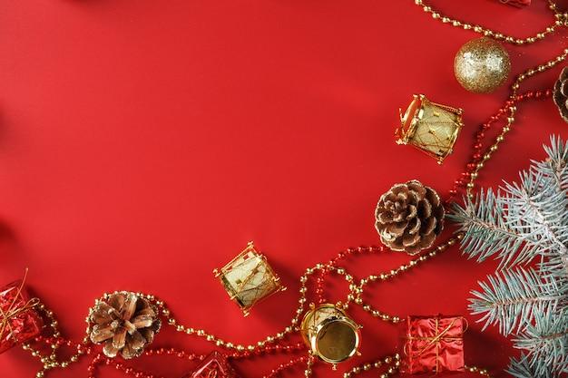 Kerststuk van kerstversieringen en kerstboomversieringen op een rode achtergrond. vrije ruimte voor tekst.