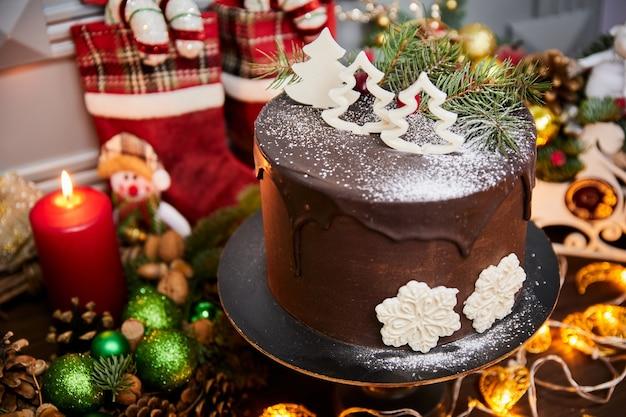 Kersttaart gemaakt van chocoladebasis met chocoladecrème versierd met kerstbomen