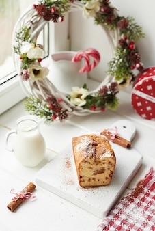 Kersttaart, melk, cacao met marshmallows, kaneel bij het raam