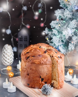 Kersttaart met rozijnen en gekonfijt fruit met kerstdecor en kaarsen, stilleven