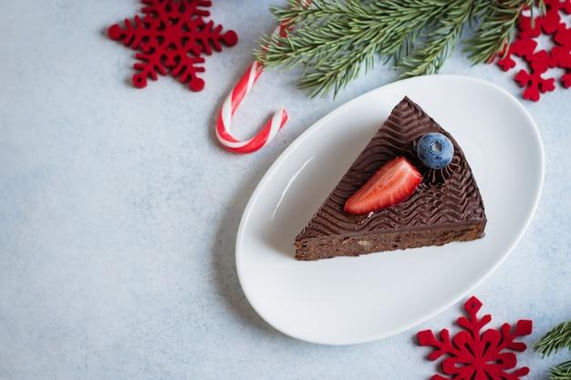 Kersttaart voor het dessert. heerlijk stuk van chocoladecake met kopje koffie en melk op blauwe steen concrete tafel. ontbijt eten concept. feestelijke feestdecoratie