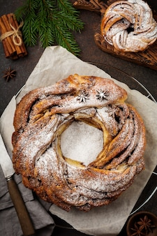 Kersttaartbroodje met kaneel en poedersuiker op een donker oud beton