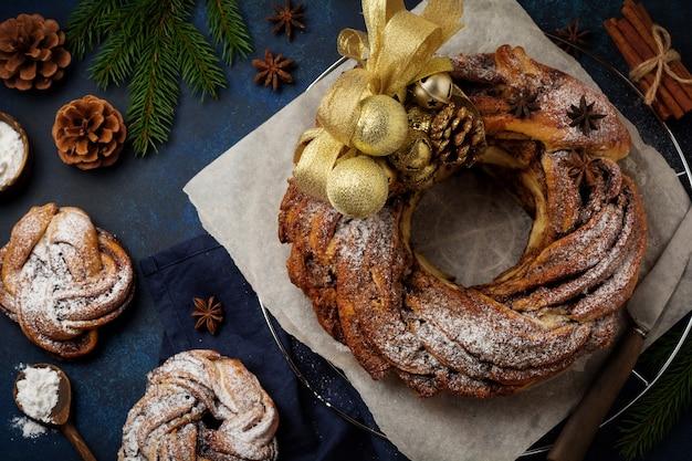 Kersttaartbroodje met kaneel en poedersuiker op een donkere oude betonnen of stenen ondergrond