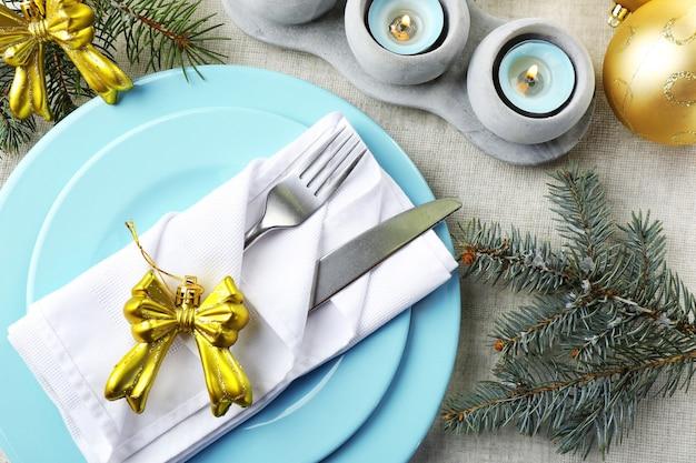 Kersttafel in blauwe, gouden en witte kleuren op een grijze tafelkleedachtergrond