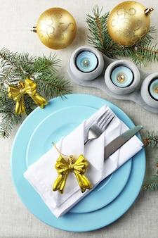 Kersttafel in blauwe, gouden en witte kleuren op grijs tafelkleed