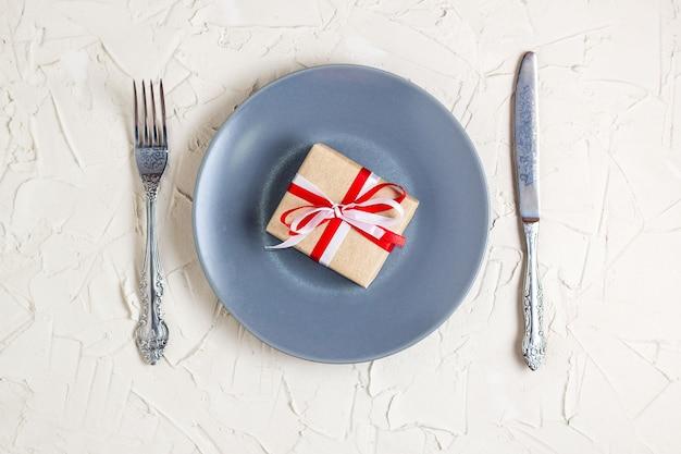 Kersttafel instelling met grijze plaat geschenkdoos en zilverwerk
