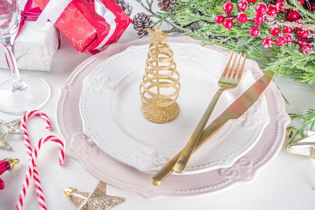 Kersttafel instelling met lege borden, geschenkdoos en kerstdecor