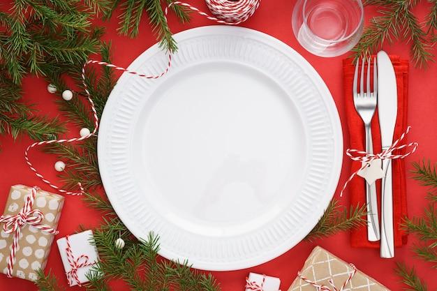 Kersttafel instelling met lege plaat, bestek en geschenkdozen