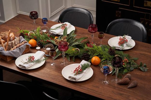 Kersttafel instelling met witte platen en kerstboom op houten tafel, bovenaanzicht.