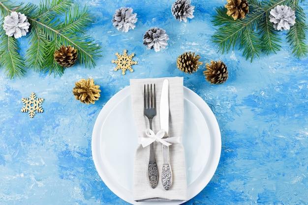 Kersttafel met borden, bestek, geschenkdoos en versieringen op blauwe tafel. bovenaanzicht