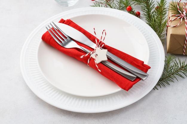 Kersttafel met borden, rood servet, vork en mes