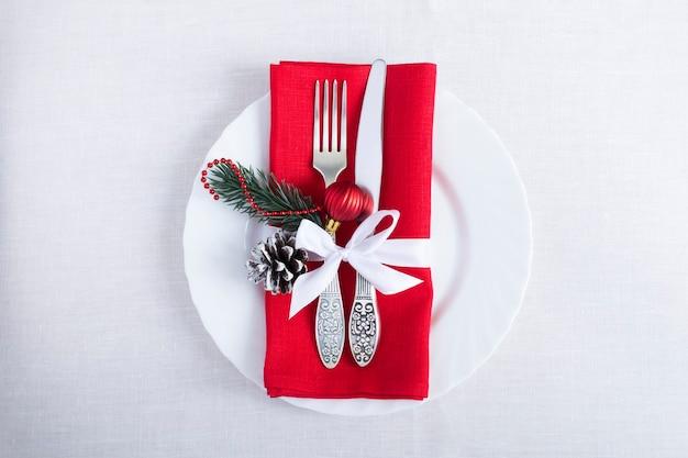 Kersttafel met een rood servet op het witte tafelkleed. bovenaanzicht. ruimte kopiëren.